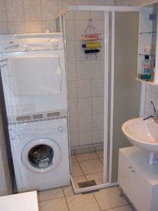 Torktumlare, tvättmaskin, duschkabin och handfat i ett litet badrum.